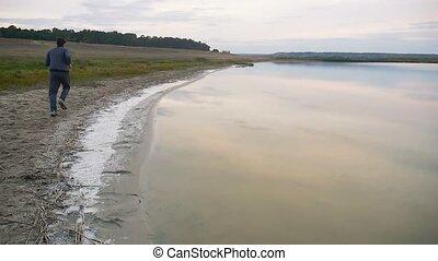 man athlete runs runner on sport nature near a lake healthy...