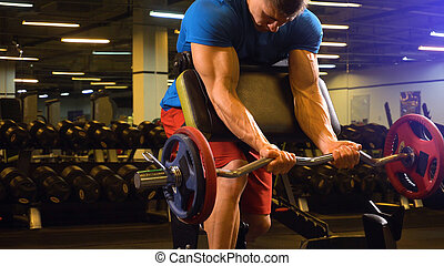 Man athlete trainer showing how to make excersis on biceps