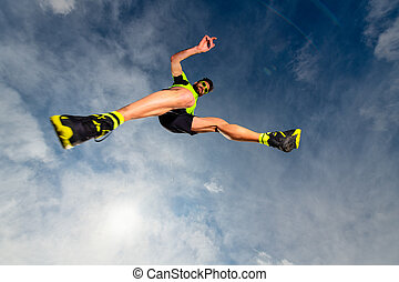 Man athlete while jumping during a trail running in the mountains