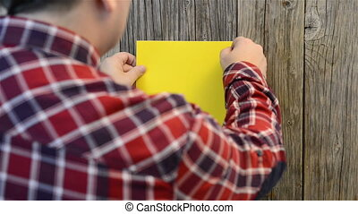 Man attaches yellow paper sheet on old wood wall board