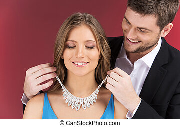 Man attaching necklace to girl's neck. man standing behind...