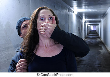 Man attacks a woman from behind in a dark tunnel