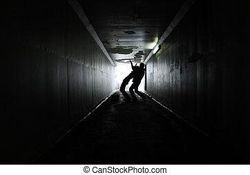 Man attacks a woman in a dark tunnel - Silhouette of a man...