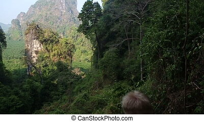 man backside view looks at canyon cliffs in jungle
