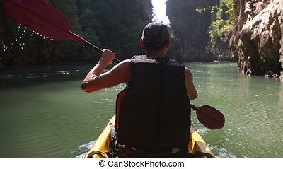 man backside view rows on kayak in canyon