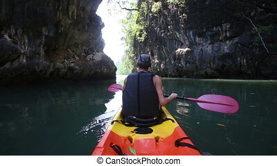 man backside view rows on kayak out to sea