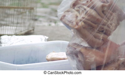 Man bags uncooked pork skin into a plastic bag for...