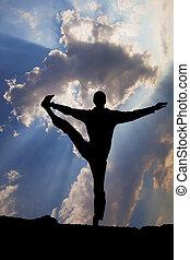 Man balance in yoga tree pose on ocean beach at sunset