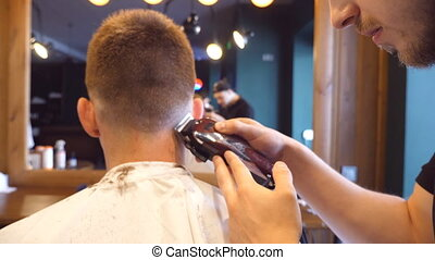 Man barber cutting hair of male client with clipper at...