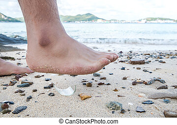 Man barefoot walking on the beach,