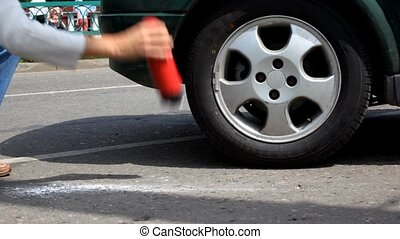 Man beats foaming fire extinguisher on asphalt near...