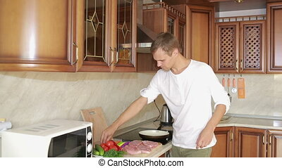 Man Beats Meat By Kitchen Hammer. man preparing dinner