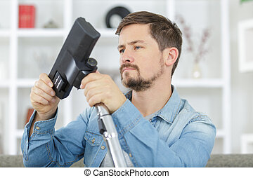 man before hoovering carpet with vacuum cleaner