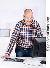 Man behind an office desk looking at the computer