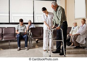 Man Being Helped By Nurse To Walk Zimmer Frame - Senior man...