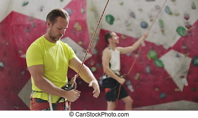 Man belaying another climber on an indoor climbing wall. A...