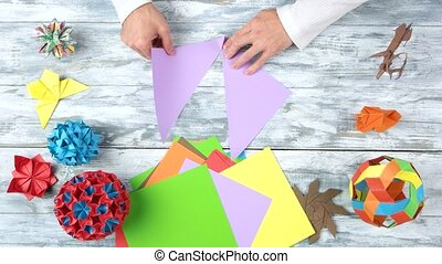 Man bend paper to make origami. Different origami figures on...