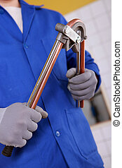Man bending copper pipe