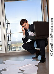 Male entrepreneur bending down to collect scattered papers while talking on cell phone