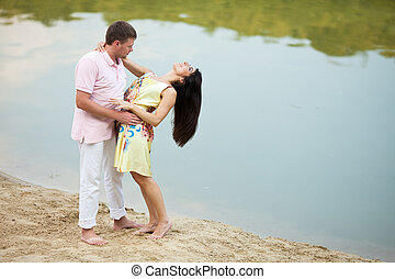 Man bends brunette over standing on the lake shore
