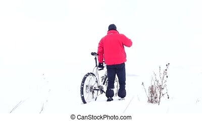 Man biker is pushing bike in deep snow at dry bush of thistle . Cloudy winter day with gentle wind and small snow flakes in the air.