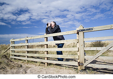 man birdwatching 2 - White adult male resting on fence using...