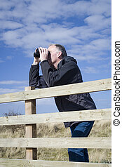 Man birdwatching 3 - Middle aged white male bird watching in...