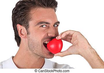 Man biting heart-shaped object