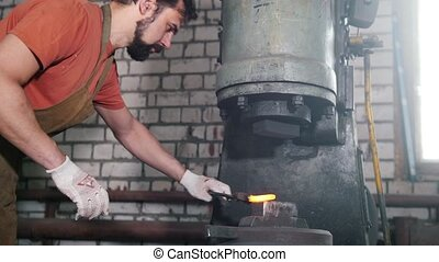 Man blacksmith forges the metal at the mechanical hammer -...