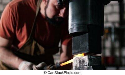 Man blacksmith in workshop forging red hot iron on anvil -...