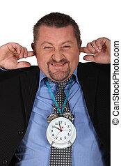 Man blocking his ears because of alarm clock