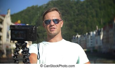 man, blogger using a camera, walking in the city on a hot...