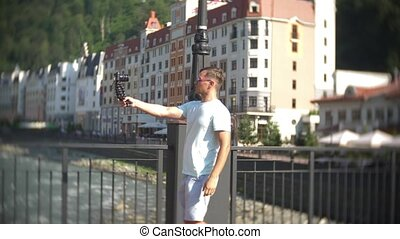 man, blogger using a camera, walking in the city on a hot sunny day. Travel. The concept of a way of life. gadget of modern communication technologies. 4k, slow motion