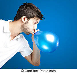 man blowing balloon