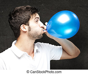 man blowing balloon - portrait of young man blowing a...