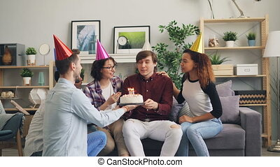 Man blowing candles on birthday cake, friends congratulating...