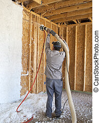 Man blowing insulation into the wall