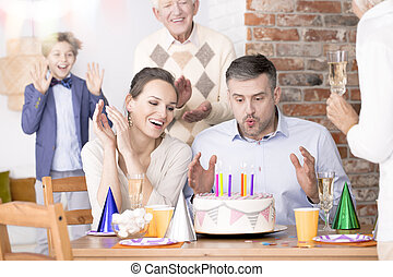 Man blowing out candles