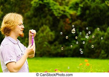 Man blowing soap bubbles outdoor