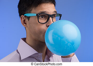 Man blowing up balloon on blue background. portrait of young...