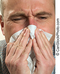 Man blows his nose in a handkerchief