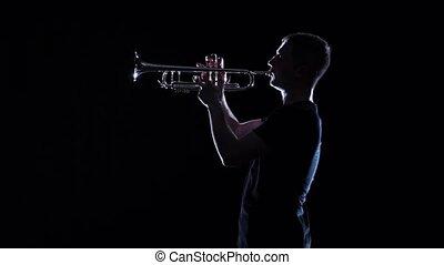 Man blows motif in wind instrument. Black studio, slow motion