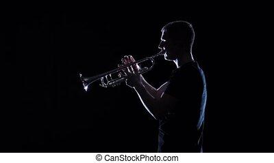 Man blows motif on wind instrument in slow motion. Studio