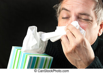 Close-up of a man blowing his nose while holding a tissue box.