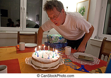 man blows out his birthday cake