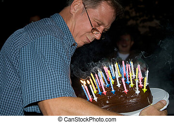 man blows out his birthday candles at the birthday