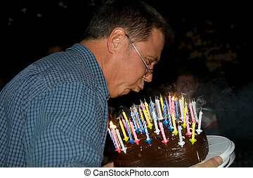 man blows out his birthday candles