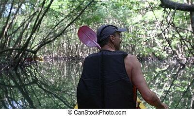 man boating in kayak along lagoon