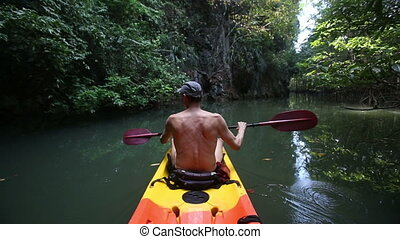 man boating in kayak along lagoon - elder bare trunk man is...