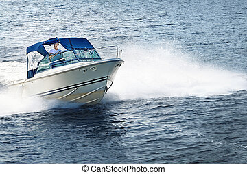 Man boating on lake - Man piloting motorboat on lake in...